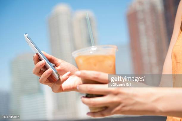 Hispanic woman holding cell phone and iced coffee