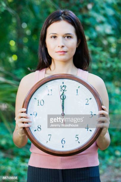 Hispanic woman  holding clock in forest