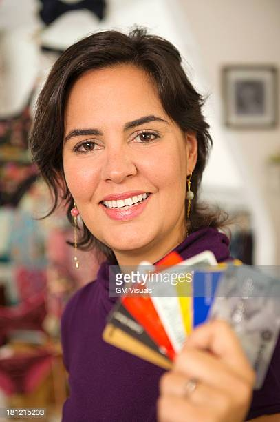 Hispanic woman holding credit cards in shop