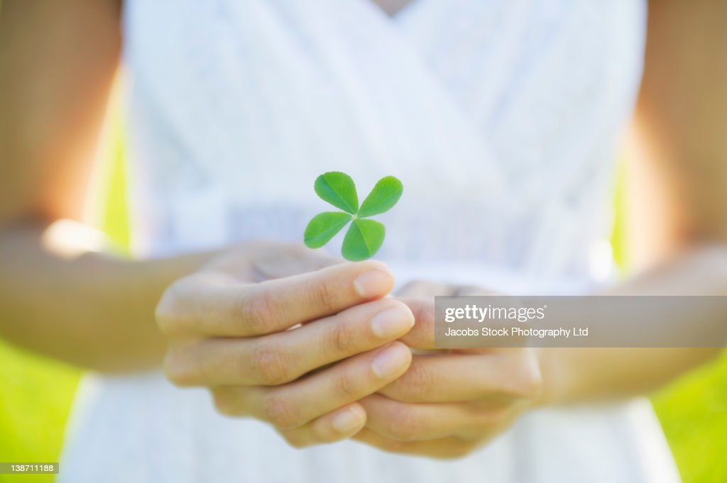 Hispanic woman holding four-leaf clover : Stock Photo