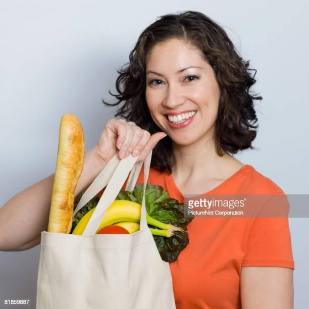 Hispanic woman holding grocery bag