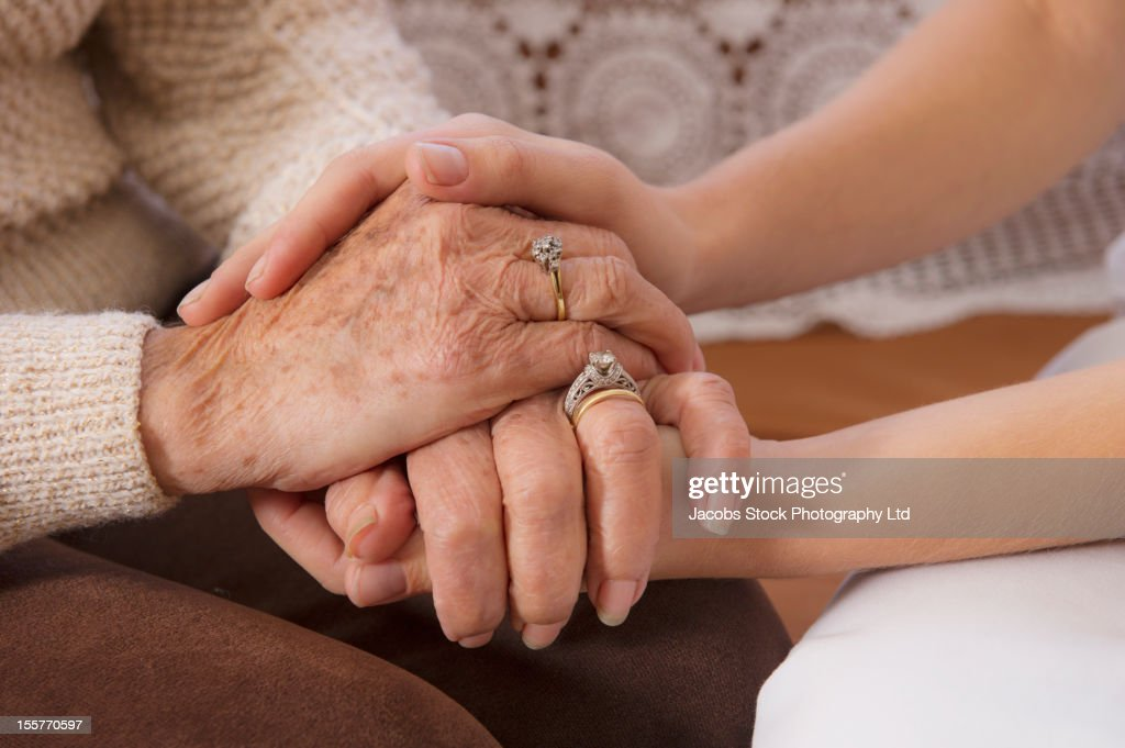 Hispanic woman holding hands with senior woman : Stock Photo
