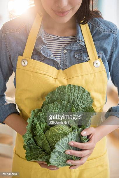 Hispanic woman holding head of lettuce