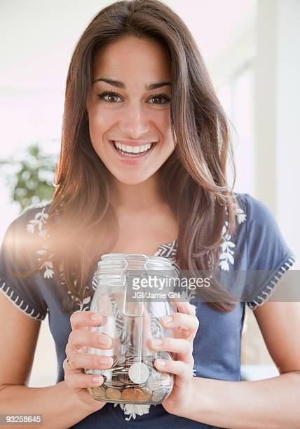 Hispanic woman holding jar of coins