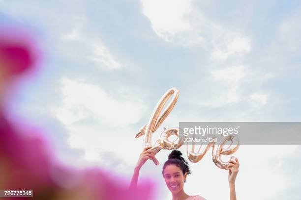 Hispanic woman holding love balloon outdoors