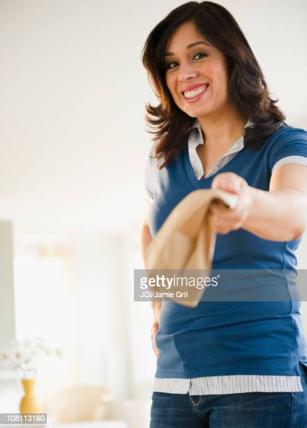 Hispanic woman holding out paper bag