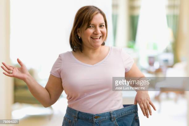 Hispanic woman holding out waistband of pants