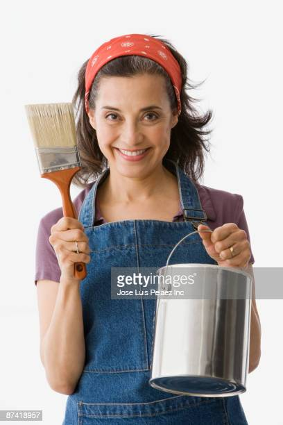 hispanic woman holding paint brush and paint can - bricolage humour photos et images de collection