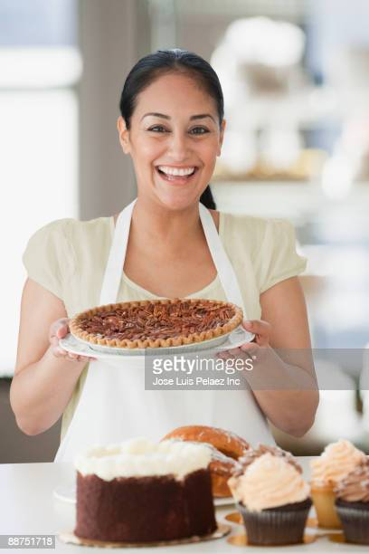 Hispanic woman holding pie in bakery