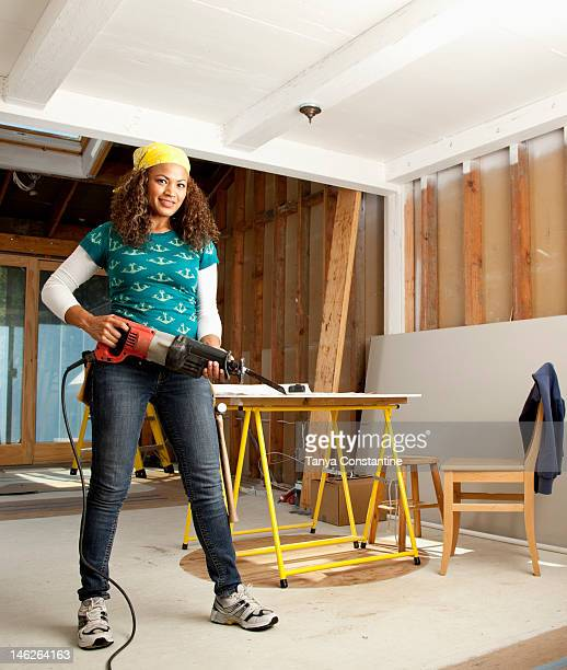 hispanic woman holding power tool - tanya constantine stock pictures, royalty-free photos & images
