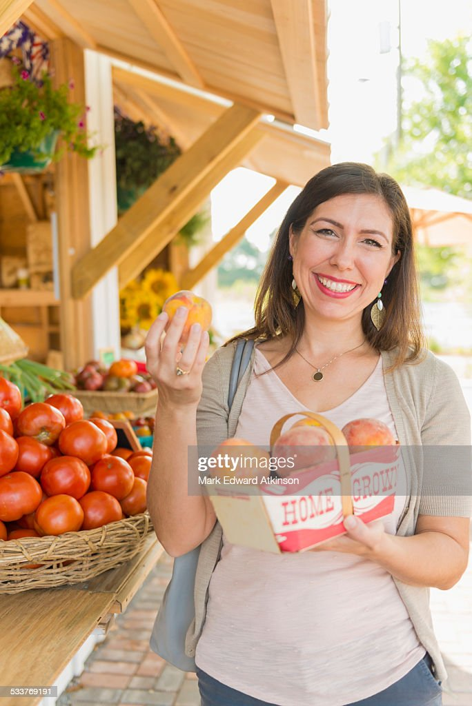 Hispanic woman holding produce at farmers market : Foto stock