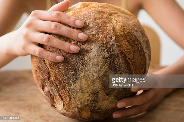 Hispanic woman holding round loaf of bread