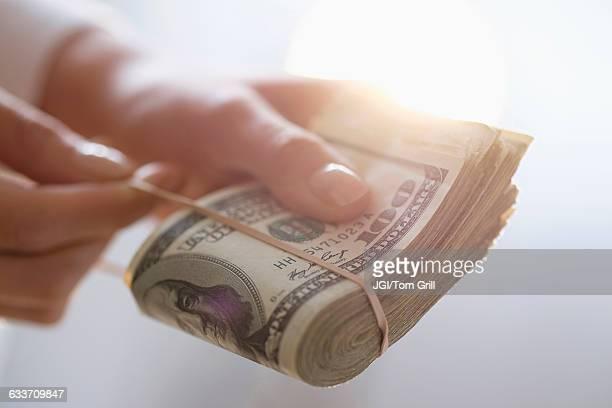 Hispanic woman holding rubber band around wad of cash