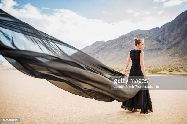 Hispanic woman holding scarf in remote desert