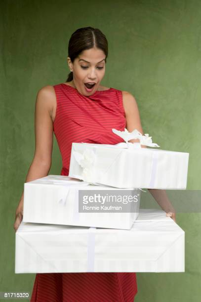Hispanic woman holding stack of gifts