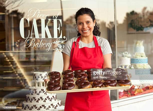 Hispanic woman holding tray of doughnuts