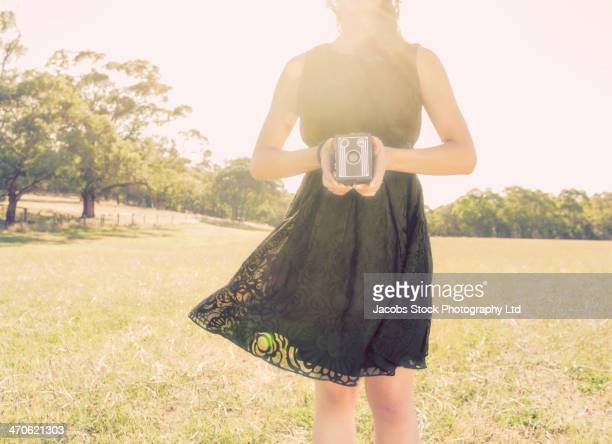 Hispanic woman holding vintage camera
