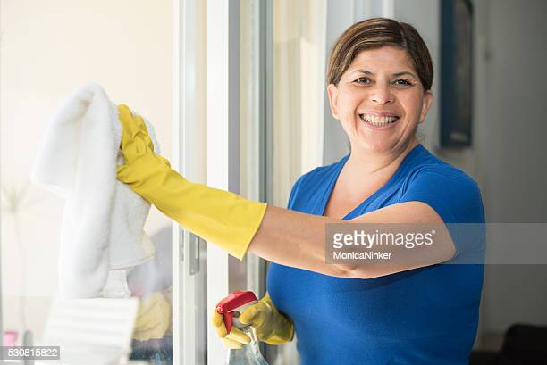 hispanic woman housekeeping - window cleaning stock photos and pictures