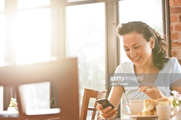 Hispanic woman in cafe using cell phone