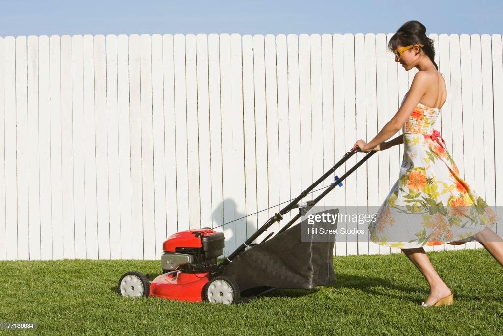 Hispanic Woman In Dress Pushing Lawn Mower Stock Photo