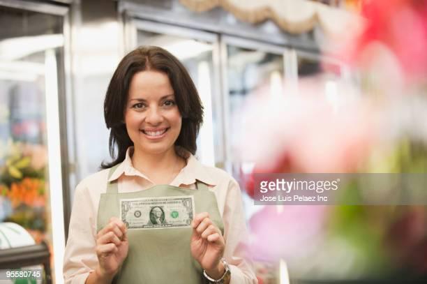Hispanic woman in florist shop holding first dollar bill