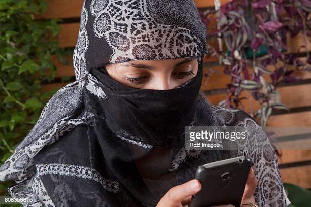 hispanic woman in headscarf using cell phone - burka stock-fotos und bilder