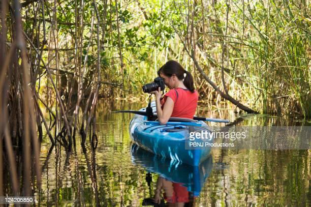 Hispanic woman in kayak photographing everglades
