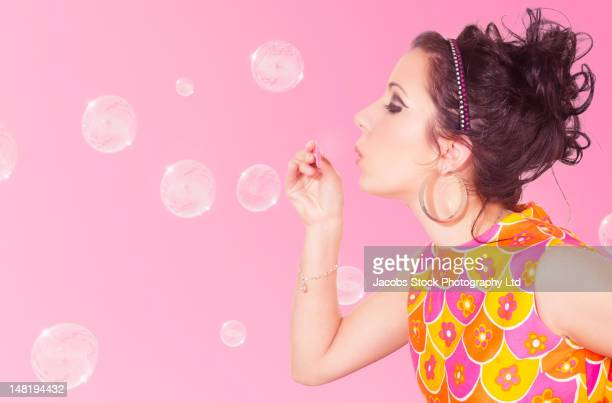 Hispanic woman in nostalgic dress blowing bubbles