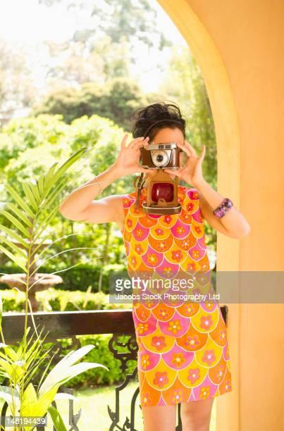Hispanic woman in nostalgic dress using retro camera
