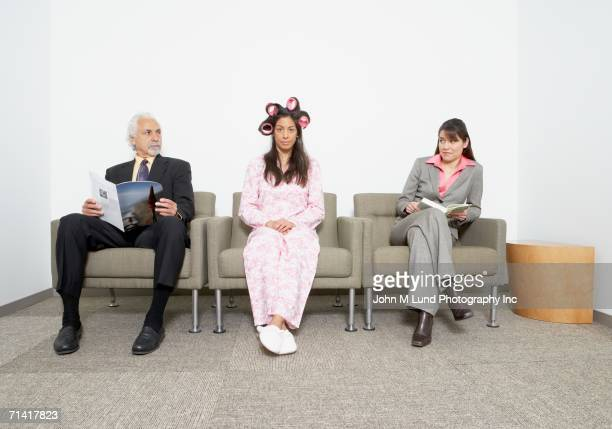 Hispanic woman in pajamas and curlers sitting next to business people