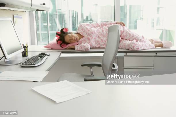 hispanic woman in pajamas and curlers sleeping on her desk - dormir humour photos et images de collection