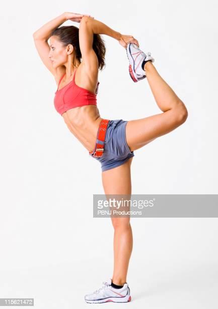 Hispanic woman in sportswear lifting leg in air