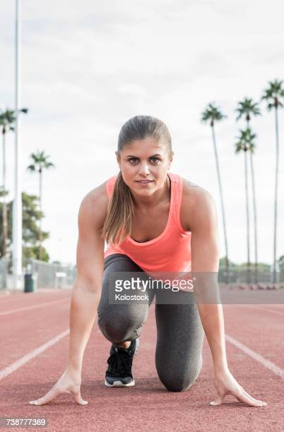 Hispanic woman in starting position on track