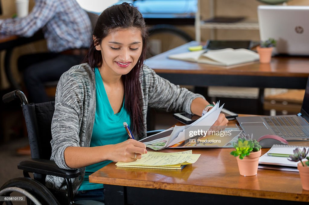 Hispanic woman in wheelchair in an office working on assignment : Stock Photo