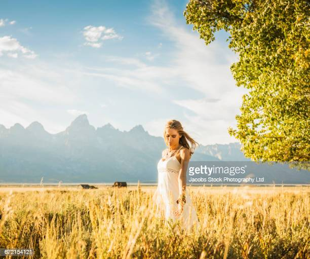 Hispanic woman in white dress standing in tall grass