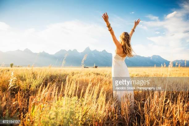hispanic woman in white dress with arms raised in tall grass - weißes kleid stock-fotos und bilder