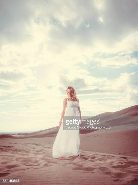 hispanic woman in white gown standing on sand dune - 白のドレス ストックフォトと画像