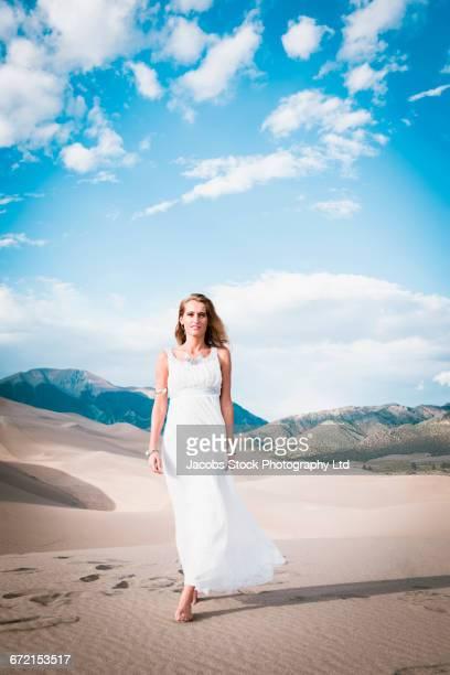 hispanic woman in white gown walking on sand dune - 白のドレス ストックフォトと画像