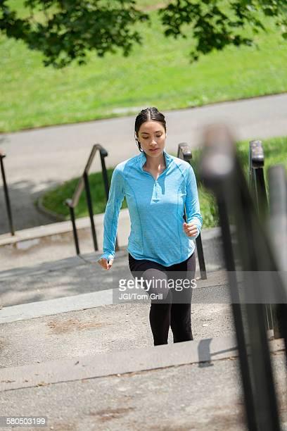 Hispanic woman jogging on city steps