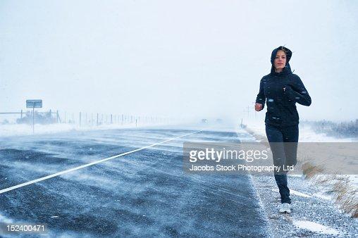 Hispanic woman jogging on snow covered road