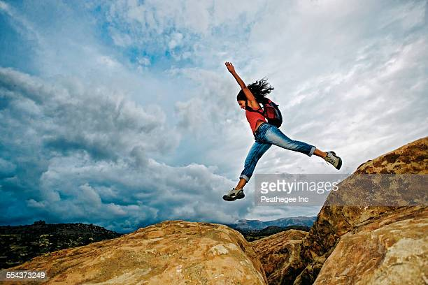 hispanic woman jumping crevasse on rock formation - bridging the gap stock pictures, royalty-free photos & images