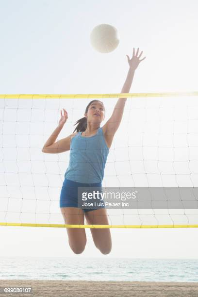 Hispanic woman jumping for volleyball