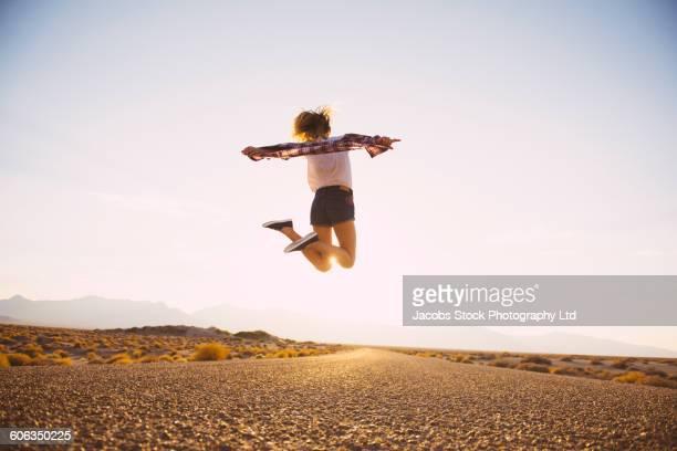 Hispanic woman jumping on remote road