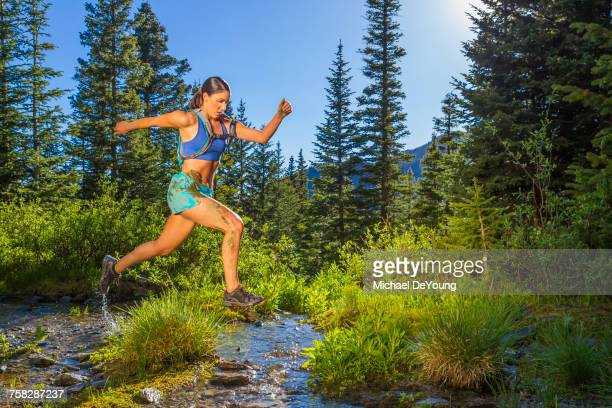 hispanic woman jumping over stream - cross country running stock pictures, royalty-free photos & images