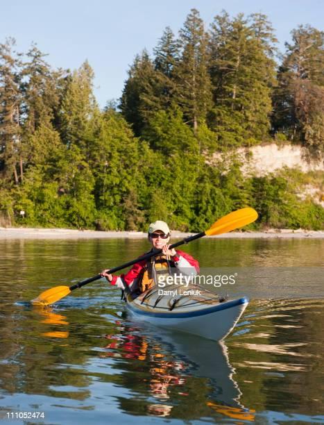 Hispanic woman kayaking on lake