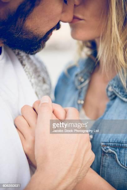 Hispanic woman kissing nose of boyfriend