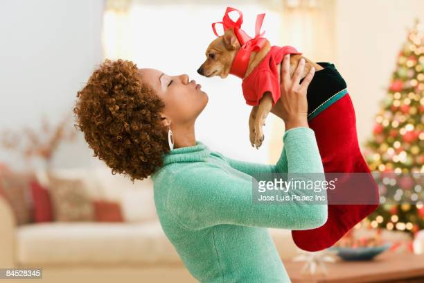 Hispanic woman kissing pet dog in costume