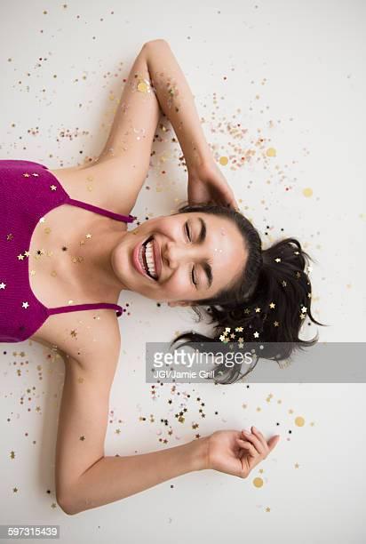 Hispanic woman laying in confetti