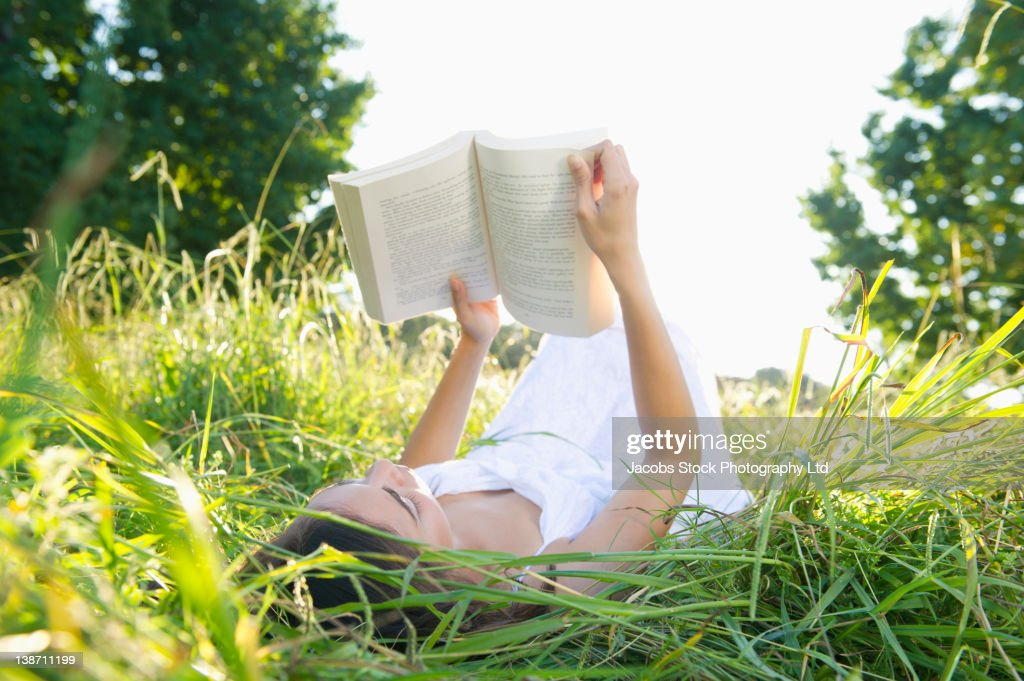 Hispanic woman laying in grass reading book : Stock Photo