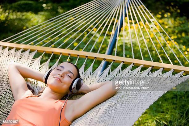Hispanic woman laying in hammock listening to headphones